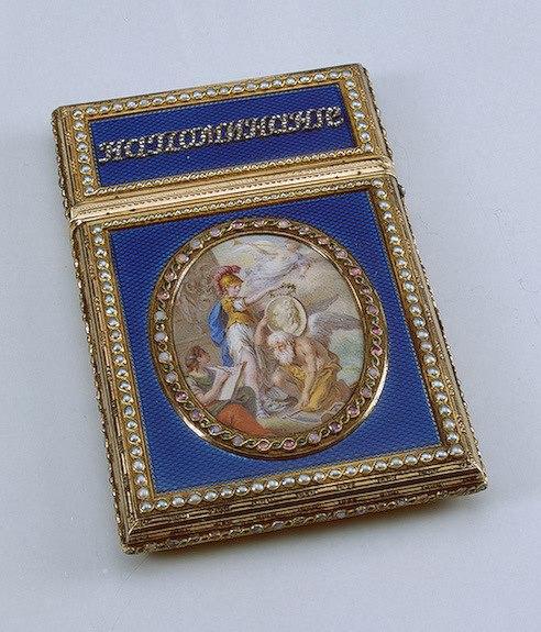 """Золотое карне, покрытое прозрачной синей эмалью по гильошированному (гравированному) фону, было преподнесено императрице Екатерине II князем Г.А. Потемкиным. Оно имеет декор из полужемчуга, опалов, изумрудов и надпись, выполненную алмазами с двух сторон: """"НАПОМИНАНИЕ"""" - """"БЛАГОДАРНОСТИ"""". Лицевая и оборотная стороны футляра украшены медальонами расписной эмали. На одном богиня мудрости Минерва венчает лавровым венком портрет Екатерины II, поддерживаемый коленопреклоненным богом времени Хроносом, и муза истории Клио с раскрытой книгой. На втором - изображение фигур воина и гения Славы перед жертвенником с надписью: """"Тобою восхожу""""."""