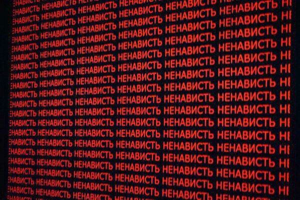 """Экран, заполненный множеством слов """"ненависть"""" красными буквами"""