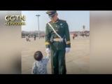 Маленький мальчик салютует солдатам почетного караула в Пекине на площади Тяньаньмэнь