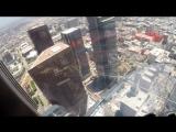 Репортер прокатился по стеклянной горке на горке на небоскребе
