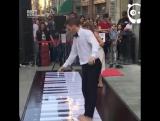 Пара играет на огромном пианино